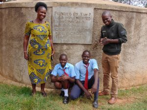 The Water Project:  Principal Alashu And Field Officer Samuel Samidi With Dominic And Another Student At The Rain Tank