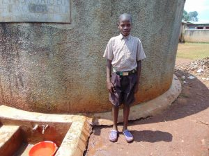 The Water Project:  Student Stands Proud At Rain Tank