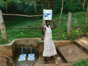 The Water Project:  Woman Carries Water Home