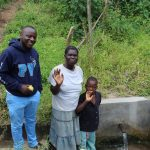 The Water Project: Ewamakhumbi Community, Yanga Spring -  Field Officer Allan Amadaro With Hellen And Robinson