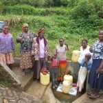 The Water Project: Emachembe Community, Hosea Spring -  Happy Spring Users With Field Officer Betty