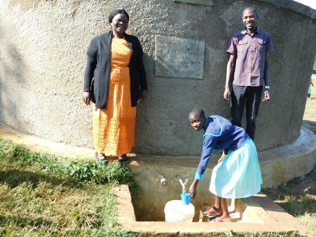 The Water Project : 5-kenya18310-head-teacher-osundwa-vivian-and-field-officer-protus-at-the-rain-tank