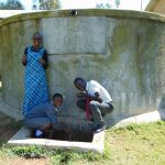 The Water Project: St. John Cheptech Secondary School -  Field Officer Joan With Students At The Rain Tank
