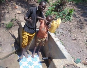 The Water Project:  Alex Injendi With A Child At The Spring