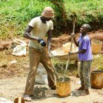The Water Project: Lutonyi Community, Lutomia Spring -  Boy Helps Artisan Mix Plaster