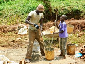 The Water Project:  Boy Helps Artisan Mix Plaster