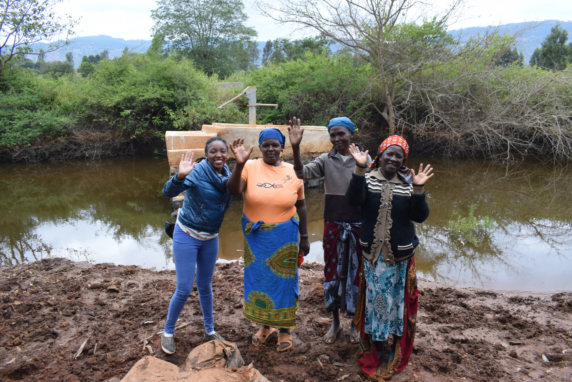 The Water Project : kenya18194-field-officer-kendi-and-community-members-at-the-well-a-year-later