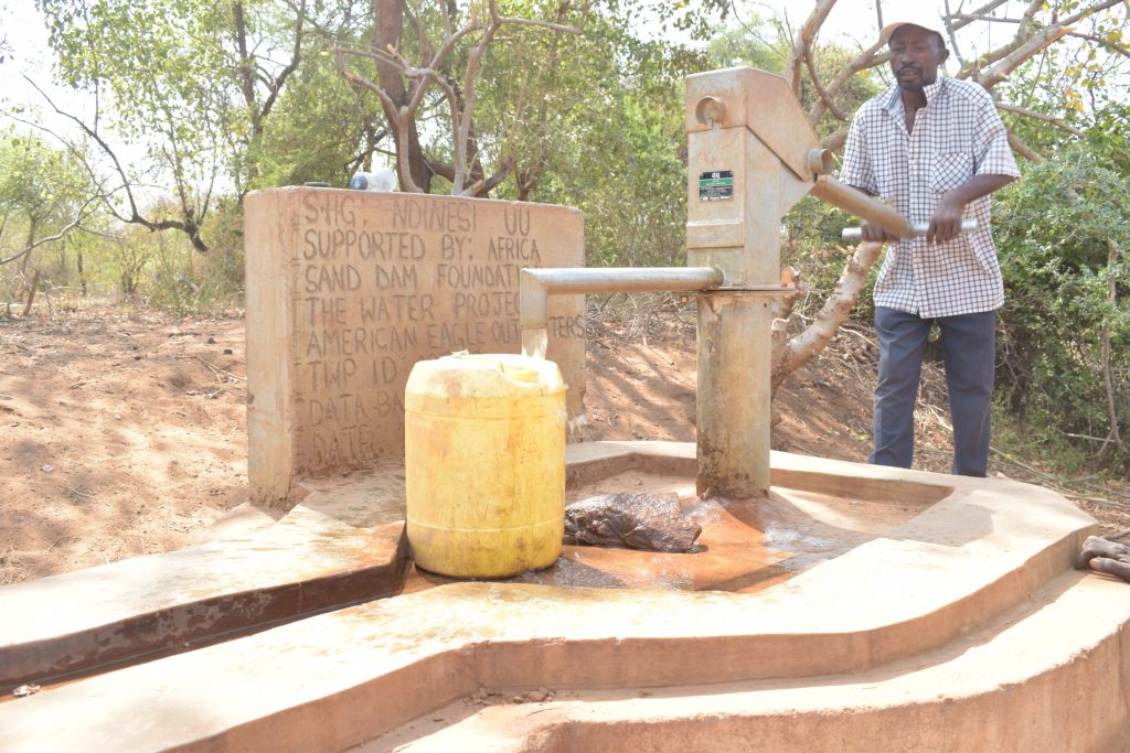 The Water Project : kenya18279-filling-up-container-at-the-well-a-year-later