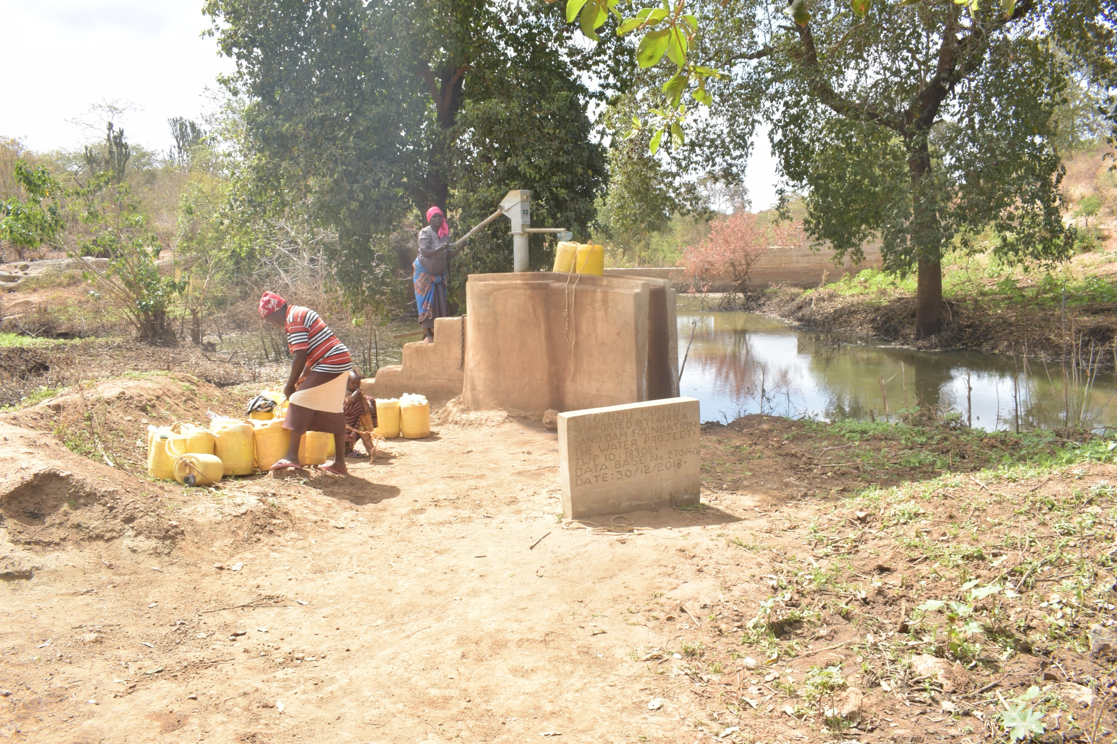 The Water Project : kenya18307-collecting-water-at-the-well-a-year-later