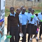 The Water Project: Kyamatula Secondary School -  Students Lined Up To Get Water From The Tank