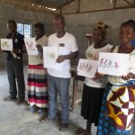The Water Project: 45 Main Motor Road, The Redeemed Christian Church of God -  Community Members Are Shown Displaying Disease Transmission Story Posters