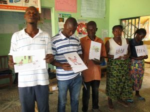 The Water Project:  Community Members Hold Disease Transmission Posters