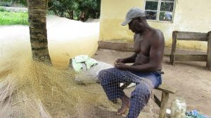 The Water Project:  Old Man Making Fishing Net