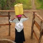 The Water Project: Rubana Yagilewo Community -  Kunihira Roselyne Lifts Water Container