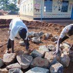 The Water Project: Goibei Primary School -  Laying Stones For Rain Tank Foundation