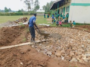 The Water Project:  Adding Cement To Stone Foundation Of Rain Tank