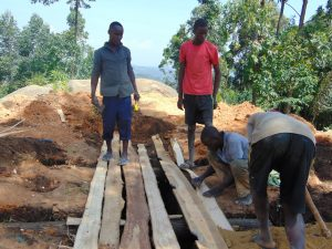 The Water Project:  Fitting Lumber Over Latrine Pits