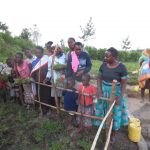 The Water Project: Chegulo Community, Sembeya Spring -  Community Members Bring Grass To Plant Over Springbox