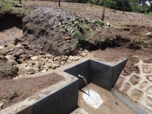 The Water Project:  Backfilling With Stones As Water Starts To Flow