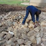 The Water Project: Ematiha Secondary School -  Adding Stones To Rain Tank Foundation