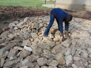 The Water Project:  Adding Stones To Rain Tank Foundation
