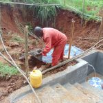 The Water Project: Shamakhokho Community, Imbai Spring -  Adding Plastic Tarp Over Backfilled Layers