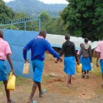 The Water Project: Kapsaoi Primary School -  Students Arrive At School Carrying Water