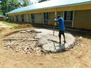 The Water Project:  Pouring Cement Over Stone Rain Tank Foundation