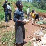 The Water Project: Shamakhokho Community, Imbai Spring -  Community Members Delivers A Stone