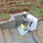 The Water Project: Shamakhokho Community, Imbai Spring -  Village Elder Damaris Fetches Water