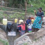 The Water Project: Chegulo Community, Sembeya Spring -  Betty With Children Celebrating The Spring
