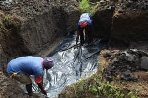 The Water Project:  Laying Plastic Tarp Before Laying Foundation