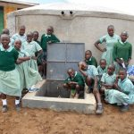 The Water Project: Mukangu Primary School -  Students And Staff Pose With Rain Tank