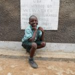 The Water Project: Mukangu Primary School -  Student In Front Of Boys Latrines