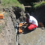 The Water Project: Chegulo Community, Sembeya Spring -  Brick Setting