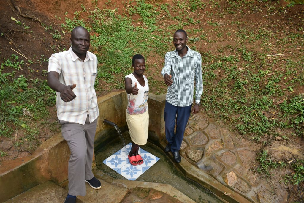The Water Project : 7-kenya18313-patrick-nyanje-charity-njilu-and-field-officer-protus-by-the-spring