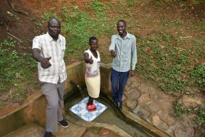 The Water Project:  Patrick Nyanje Charity Njilu And Field Officer Protus By The Spring