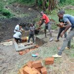 The Water Project: Bung'onye Community, Shilangu Spring -  Kids Help Pass Bricks