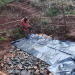 The Water Project: Mushina Community, Shikuku Spring -  Backfilling With Stones And Plastic Tarp