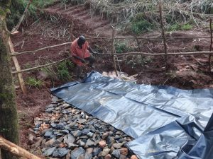 The Water Project:  Backfilling With Stones And Plastic Tarp