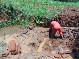 The Water Project:  Opening Up Drainage Channel To Divert Water