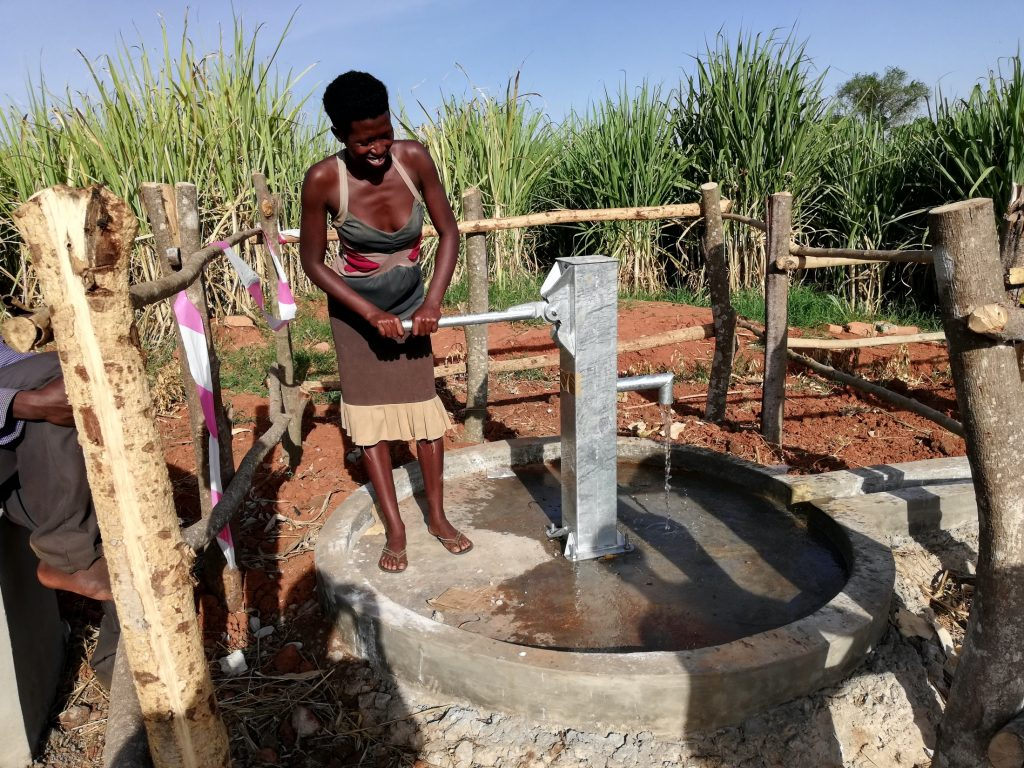 The Water Project : uganda19280-woman-happily-pumps-water-from-the-well