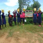 The Water Project: Jinjini Friends Primary School -  Students Carrying Water To School