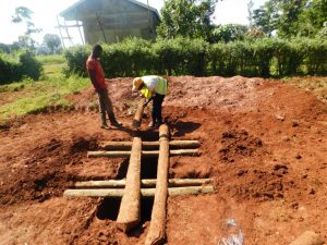The Water Project:  Laying Timber Over Latrine Pits