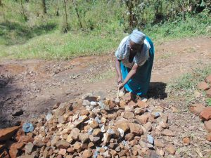 The Water Project:  Elderly Woman Helps Crush Rocks To Gravel