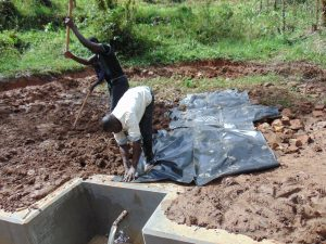 The Water Project:  Backfilling With Soil And Plastic Tarp