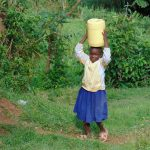The Water Project: Boyani Primary School -  Student Carrying Water