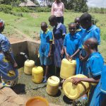 The Water Project: St. Michael Mukongolo Primary School -  Students Fetch Water Alongside Community Member