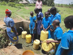 The Water Project:  Students Fetch Water Alongside Community Member