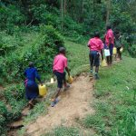 The Water Project: Jinjini Friends Primary School -  Students Carrying Water Back To School